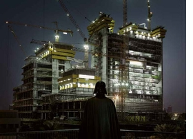 """Featured image, """"Darth Vader, Dubai,"""" 2009, is reproduced from French photographer Cédric Delsaux's delightfully surprising new monograph, <a href=""""9782915173703.html"""">Dark Lens</a>. Treated to a glowing full-page review in the December 11 <a href=""""blog-dark-lens-press.html"""">New York Times</a>, the work """"wasn't born to pay homage to R2-D2, Luke Skywalker and their buddies,"""" according to <a href=""""http://www.nytimes.com/2011/12/11/arts/design/cedric-delsauxs-photographs-of-star-wars-on-earth.html"""" target='new'>The Times'</a> Dana Jennings. """"'My first intention wasn't to produce a series on <I>Star Wars,</I> but to photograph locations that are the makeup of our modernity: parking lots, peripheral zones, wastelands, forgotten places, of both beauty and ugliness, common and mad,' Mr. Delsaux said by e-mail. 'Nevertheless, something was missing, my images were flat, déjà vu. I then had the idea to add these sci-fi characters, with the immediate effect of making my primal sensations stand out, the fantastical nature of the characters invading the whole frame, both universes harmoniously coming together.'"""""""