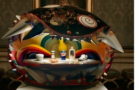 """In the Salon des Nobles, amidst the fine furniture designed by Riesener, Takashi Murakami presents <i>The Simple Things</i> � the result of a collaboration with musician and hip-hop producer Pharrell Williams, who makes his first foray into contemporary art with this piece. Seven sculptures representing everyday objects (soda can, condom, packet of nacho chips) are set in gold with thousands of precious stones. Takashi Murakami devised a brightly lit display case inspired by one of his characters, Mr. Dob.<p> These everyday objects � �Proust�s madeleine� � la Pharrell Williams � are displayed in all their majesty inside Mr. Dob�s mouth. This dazzling set celebrates the encounter between popular culture and the luxury world, which Takashi Murakami has often conquered with brio.<P> Featured image and text are reproduced from <a href=""""9782915173727.html"""">Murakami Versailles</a>."""