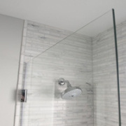 Frameless shower shield has seals between the glass and wall to keep the water in