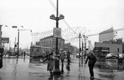 Looking south at The Junction, 1951, with girl distributing pamphlets