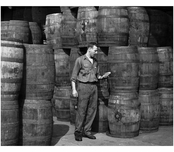 Stanley Hyams, co owner of Washington Pickle Works, in a room full of barels of pickles 1959