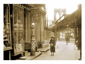 woman walking past shop with the Brooklyn Bridge in the background
