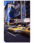 Yellow cabs pass through 1970s Times Square