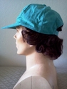Teal baseball cap with human hair attached