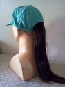 Teal cap with short dark brown straight pony tail