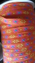 Orange jacquard ribbon with yellow and fuchsia daisy flower trim 1/2 inch