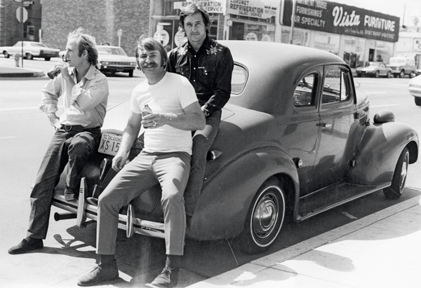Joe Goode, Jerry McMillan and Ed Ruscha in front of their studios on Western Avenue, Hollywood, 1970.  ED RUSCHA [in the parking area outside his studio] Let me show you something. [Starts up an old black Ford. It