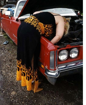 "Featured image, ""Patty working on car in flame outfit"" (2003), is reproduced from <I>Lisa Kereszi: Joe's Junk Yard.</I>"