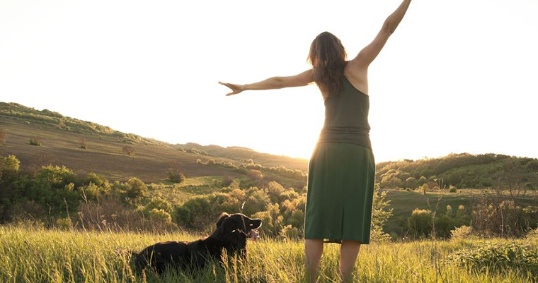 A young women and a black dog facing to sun set