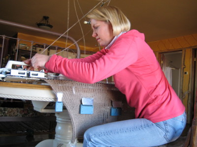 Meredith at knitting machine with blanket hanging down from it.