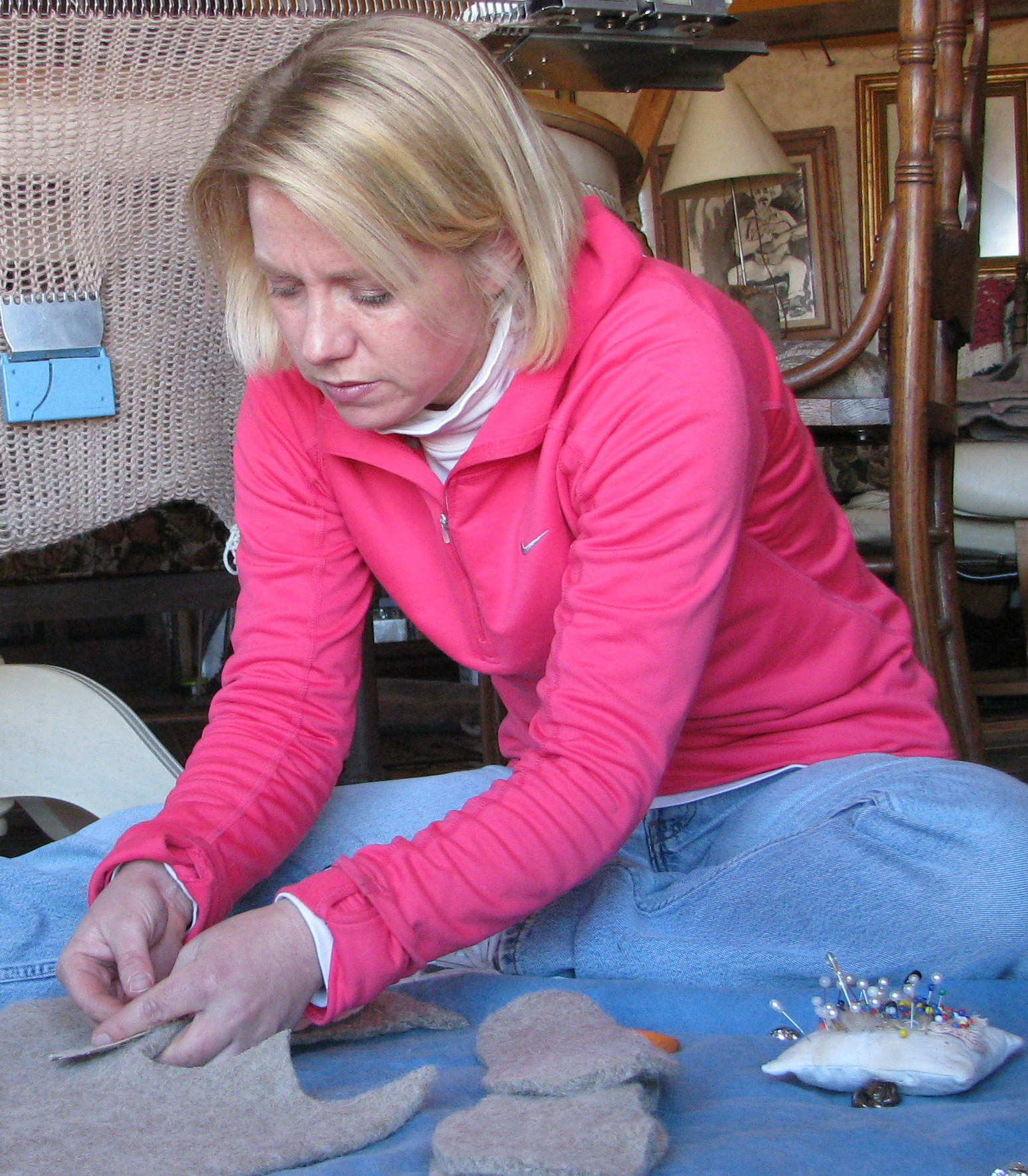 Meredith's pinning a Snuggly Toes pattern to a felted blanket of material.