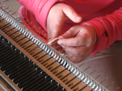 Tight shot of Meredith's hands putting alpaca yarn on knitting machine border=