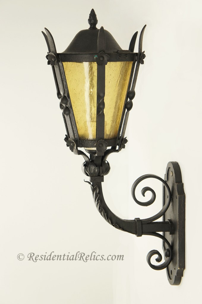 Antique wrought iron exterior wall sconce with amber glass shade, circa 1920s